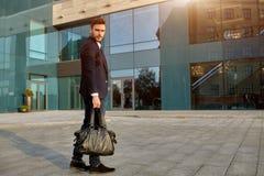 Mode för man` s En ung manlig affärsman i en moderiktig dräkt och en vit skjorta med en stor svart handväska kommer ut från en in royaltyfri foto
