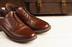 Mode för man` s med bruna läderskor och affären hänger löst på en träbakgrund Mode för man` s, skor, tillbehör, affärsbackgr Arkivbilder