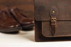 Mode för man` s med bruna läderskor och affären hänger löst på en träbakgrund Mode för man` s, skor, tillbehör, affärsbackgr Arkivfoto