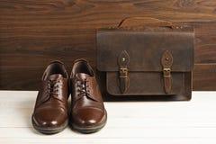 Mode för man` s med bruna läderskor och affären hänger löst på en träbakgrund Mode för man` s, skor, tillbehör, affärsbackgr Fotografering för Bildbyråer