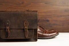 Mode för man` s med bruna läderskor och affären hänger löst på en träbakgrund Mode för man` s, skor, tillbehör, affärsbackgr Royaltyfri Foto