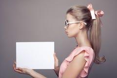 Mode-Frau in der Sonnenbrille mit leerem Papierfreiem raum in den Händen stockfotografie