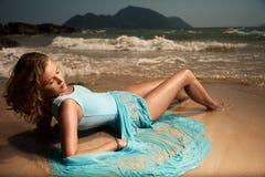 Mode-Frau im blauen Kleid, das auf Sand tropisches B liegt Stockbilder