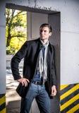 Mode geschossen: hübscher tragender Mantel und Jeans des jungen Mannes Lizenzfreies Stockbild