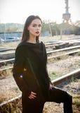 Mode geschossen: Porträt des informellen Modells des schönen Felsenmädchens im Kittel und Hosen, die am Industriegebiet der Eisen stockfotografie