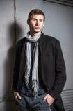 Mode geschossen: Porträt tragenden Jeans und von Mantel eines von hübschen jungen Mannes stockbild