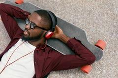 Mode Lyssnande musik för svart man i hörlurar på gatan royaltyfria foton