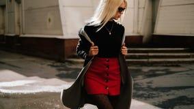 Mode-Mädchen in der modernen Kleidung Schönes Mädchen in einem Mantel und in einem roten Rock Aufstellung in der Straße lizenzfreie stockfotos