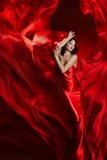 Mode-Modell Art Dress, Frauen-Tanzen im roten wellenartig bewegenden Gewebe lizenzfreie stockbilder