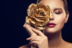 Mode-Modell Beauty Portrait mit Gold Rose Flower, goldene Frauen-Luxusmake-up Rose Jewelry lizenzfreie stockfotos
