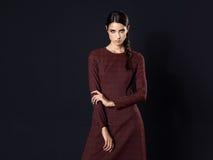 Mode-Modell, das langes kastanienbraunes Kleid auf schwarzem Hintergrund trägt Stockbild