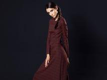 Mode-Modell, das langes kastanienbraunes Kleid auf schwarzem Hintergrund trägt Stockbilder