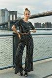 Mode-Modell, das recht in der Overall- und Haarbrötchenart auf dem Pier aufwirft Lizenzfreie Stockbilder