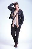 Mode-Modell, das seine Hand durch sein Haar und Lächeln führt Lizenzfreie Stockbilder