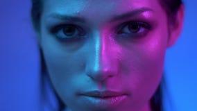 Mode-Modell in den bunten purpurroten und blauen Neonlichtern, die langsam aufwerfen und bedacht in Kamera im Studio aufpassen stock footage