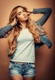 Mode-Modell in der netten Kleidung, die im Studio auf gelbem BAC aufwirft Stockfoto