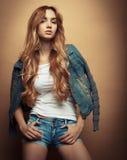 Mode-Modell in der netten Kleidung, die im Studio auf gelbem Hintergrund aufwirft Lizenzfreies Stockfoto