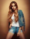 Mode-Modell in der netten Kleidung, die im Studio auf gelbem Hintergrund aufwirft Lizenzfreie Stockfotos