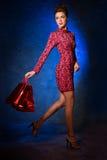 Mode-Modell in einem roten Kleid auf einem Hintergrund der Tür Beauti Lizenzfreie Stockfotos