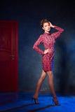 Mode-Modell in einem roten Kleid auf einem Hintergrund der Tür Beauti Stockfotos