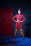 Mode-Modell in einem roten Kleid auf einem Hintergrund der Tür Beauti Lizenzfreies Stockfoto