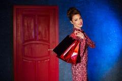 Mode-Modell in einem roten Kleid auf einem Hintergrund der Tür Beauti Stockbilder