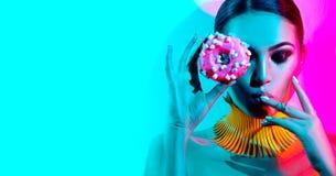 Mode-Modell-Frau, die im Studio mit Donut aufwirft Stockbild