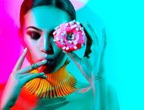 Mode-Modell-Frau, die im Studio mit Donut aufwirft Stockbilder