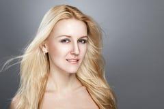 Mode-Modell Girl Portrait mit blauen Augen und dem langen blonden Haar. Schönheits-Frau lokalisiert auf einem schwarzen Hintergrun Stockbilder