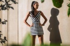 Mode-Modell im gestreiften Kleid auf einem Hintergrund lizenzfreies stockfoto