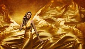 Mode-Modell im Goldkleid, Schönheits-Frau, die Fliegen-Stoff aufwirft Stockfotos