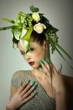 Mode-Modell im grünen Design und in den Blumen und in den Spritzpistolennägeln Stockbilder