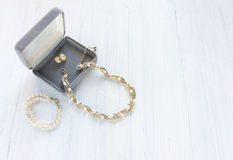 Mode-Modell Jewelry Weinleseschmuckhintergrund Schöne Gold- und Perlenhalskette, Armband und Ohrringe in einer Geschenkbox auf we stockfotos