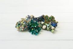 Mode-Modell Jewelry Weinleseschmuckhintergrund Schöne helle Bergkristallbrosche, -halskette und -ohrringe auf weißem Holz lizenzfreies stockfoto
