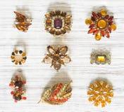 Mode-Modell Jewelry Weinleseschmuckhintergrund Schöne helle Bergkristallbrosche und -ohrringe auf weißem Holz Flache Lage, Draufs stockbilder