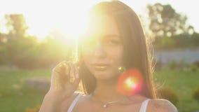 Mode-Modell-Mädchen in den goldenen Scheinen funkeln aufwerfend Porträt der Schönheit mit Funkelnkonfettis draußen stock video footage