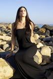 Mode-Modell mit dem schwarzen Kleid, das auf Felsen vor Meer sitzt Lizenzfreies Stockfoto