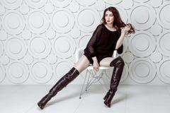 Mode-Modell mit Frisur- und smokeymake-up und rote Lippen im schwarzen Kleid und Stiefel, die auf weißem Stuhl aufwerfen stockfotos