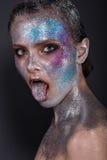 Mode-Modell mit hellem Make-up und buntem Funkeln und Scheine auf ihrem Gesicht und Körper stockfoto