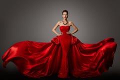 Mode-Modell Red Dress, Frau im langen flatternden wellenartig bewegenden Kleid, Schönheits-Porträt stockfotografie