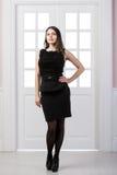 Mode-Modell-Schwarzkleid in voller Länge, das hinten in den Studiodachbodenausgangsinnentüren aufwirft Stockfotografie