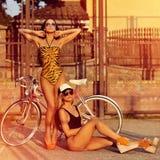 Mode-Modelle in den Badeanzügen, die draußen nahe einem Weinlesefahrrad aufwerfen Stockfoto