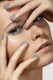 Mode-Modellgesicht mit glänzendem silbernem Make-up, Reinheitshaut u. graue Nägel manicure Lizenzfreie Stockfotos