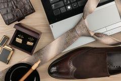 Mode och affär, anteckningsbok, skor, cufflinks, cigarr och band på en trätabell som bakgrund Royaltyfria Bilder