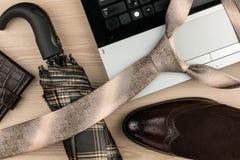 Mode och affär, anteckningsbok, skor, cufflinks, paraply på en trätabell som bakgrund ovanför sikt Arkivfoto