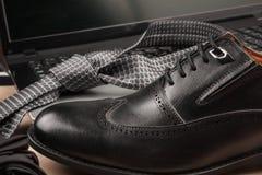 Mode och affär Skor för svart man` s står på bärbara datorn Royaltyfri Foto
