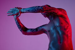 Mode photoshoot des attraktiven Mannes des Sportsitzes, der Arm herstellt auszudehnen Männlicher nackter Körper, tätowierte Hände Stockbild