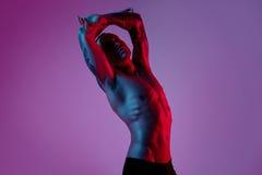 Mode photoshoot des attraktiven Mannes des Sportsitzes, der Arm herstellt auszudehnen Männlicher nackter Körper, tätowierte Hände lizenzfreies stockfoto