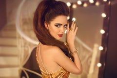 Mode-Schönheits-Mädchen-Porträt Brunettefrau in goldenem Luxusdr. Lizenzfreie Stockfotografie