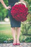 Mode som den härliga kvinnan bär den svarta klänningen, är den hållande stora buketten av 101 röda rosor Arkivbild